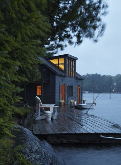 Warmly lit lake-side cottage at dusk