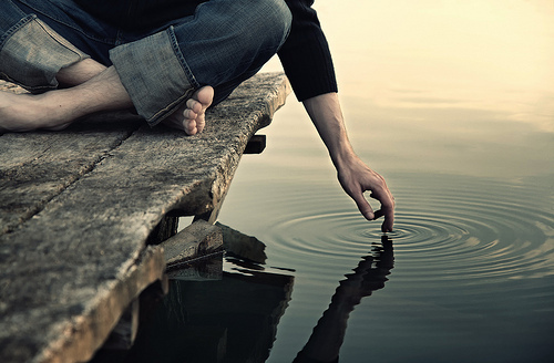 Man on a dock touching the water with finger tip